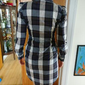 Westwood kjole fra anglomania serien. Kjolen er angivet til 44. Men passer til en 38 efter europæisk standard. Er i meget fin condition uden nævneværdige forhold. Et par mål, alle mål taget fladt liggende: ærmet fra skuldersyningen til kant 64, skulder til skulder 37, armhule til armhule 47, fuld længde ca. 100 cm