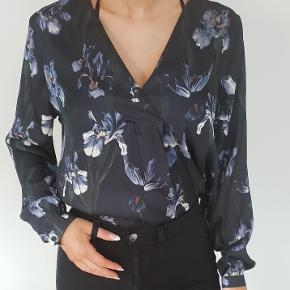 """Flot meget mørkeblå skjorte / bluse med blomster i let """"silke"""" polyester stof Str 38, passer også str 36  jeg er 171cm høj den er brugt et par gange, fremstår flot  den sælges for 180kr Den kan sendes med alm. brev postnord for 20kr kan sendes med DAO for 37,50kr"""