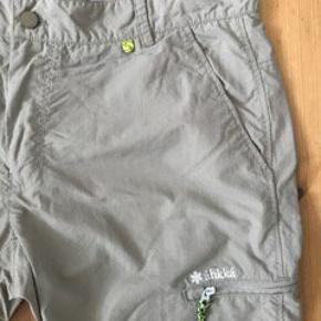 Shorts fra det svenske outdoor-mærke áhkká med praktisk lomme med lynlås på venstre bukseben. aphiTecQuick. Str. L  Farve: Lys khaki Brugt 2 gange.   Køber betaler fragt med Dao eller kan evt afhentes på Østerbro. Se også mine andre annoncer 🙂.
