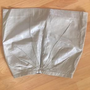 Kort nederdel i skinnende sølvgrå med rynkeeffekt foran. Lynlås bagpå. Aldrig brugt!