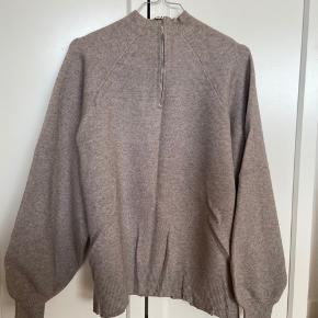 Rigtig fin strikketrøje med pufærmer som kun er brugt to gange.  Den er en smule krøllet efter at have lagt i skabet og er ikke slidt på nogen måde.
