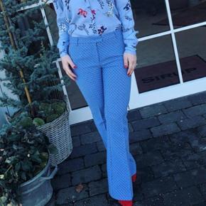 Flotte blå mønstrede bukser med vinrøde detaljer ved lommerne. Kun brugt få gange, stand som nye. Nypris 1299,-