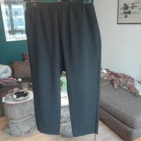 Sorte bukser i loose fit med lasercut og går til midt på læggen. Går både til sneaks og hæle.