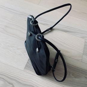 Lækker Adax sort rygtaske. God til rejsebrug. Brugt, men ingen mærker eller synlig slid.   Måler: b31 h29 d10 cm  Stropperne er 90 cm og kan justeres. Der er et lynlås rum indeni, samt et telefon rum.