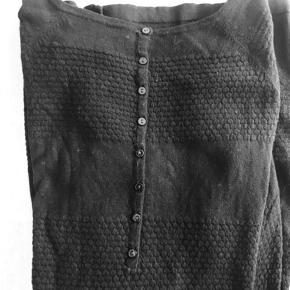 """Lækker tunika / lang bluse fra Mansted i en skøn mellemfin uld strik.  Fin struktur strik og knapdetalje i ryg.  Kan også vendes, så knapperne er foran.  Længde ca 85 cm Brystvidde ca 2 x 51 cm  """"Mansted er en personlig strikkollektion designet af Charlotte Mansted, som lægger vægt på de rene og og bløde materialer, udført med unikke strikdetaljer i materialerne: bomuld, lammeuld og yak uld. Det er klassisk og flot strik"""""""