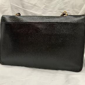 """Vintage chanel skulder taske i blød caviar.  Tasken er fra 2002-2003 og er en sesonal taske. CC-logoet er forgyldt med 24 k guld.  Tasken er blevet malet, den var hvid før, det er derfor, de er en hvid plet inde læi tasken på klappen, så man kan se chanel stemplet i guld er forholdsvist synlig (det er lidt slidt af men kan skimmes).   Der er ingen mangler eller skader på tasken uden på, men den er plettet inden i.  Tasken er 26-17-6,5 og kæden er 45 lang.  På nogle af billederne har jeg den på crossbody på sidste billede, jeg er bred over skuldrene, så den sidder højt på mig.  Tasken er autensiteret af """"etinclair autensitations"""" og af Vestiere Collective.  Sælges med Kassen, dustbag og autensitetspapier både fra VC og EA.  Jeg sender gerne flere billeder og fornuftige bud modtages."""