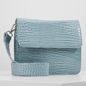 Tasken har aldrig været brugt og har derfor heller ingen brugsspor. Remmen til tasken kan nemt tages af så tasken kan bruges som clutch.