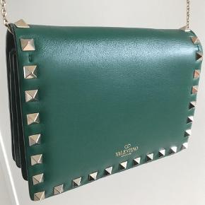 Varetype: Håndtaske Størrelse: 17 x 13 cm  Farve: Grøn Oprindelig købspris: 12000 kr. Prisen angivet er inklusiv forsendelse.  Valentino Rockstud leather cross body. Grøn med guld hardware.   I perfekt stand   Nypris 12.000,-   Mp 4.300,-