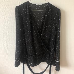 """Slå-om bluse med bindebånd. Sort med firkantede """"prikker"""""""