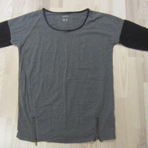 """Rigtig pæn og velholdt halvlang bluse m. 3/4 lange ærmer. Der er """"læderkant"""" rundt i halsen, og 2 små lynlåse forneden. Dejlig blød og meget elastisk kvalitet i 50% bomuld, 45% polyester & 5% elastane. Den ligger bestemt i den MEGET gode ende af """"god, men brugt"""".  Porto: 37 kr. sendt som pakke uden omdeling med DAO.  Jeg har tøj til salg til både baby, piger, drenge, kvinder og mænd i stort set alle størrelser :-) Jeg kan sende en mail med billeder/beskrivelser/priser af de størrelser du er interesseret i. Så skal jeg blot have din mailadresse :-)"""