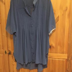 Flot og florlet skjorte fra MAT. Meget velholdt.  Korte, kantede ærmer. Knappes foran og har fine læg på front.   Lidt længere bagpå.   95 cm målt midt beg i længde.    Størrelsen hedder O/S - jeg er str 48 og passer den fint.   Farven er mellemblå/denimblå.     Sælges for 200 inkl DAO forsendelse.   Ingen bytte.  Kortærmet Farve: Blå