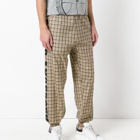 Fede Astrid Andersen bukser i beige med ternet mønster og logo langs siderne. Super lette og lækre at have på! Kan sende billeder af bukserne ved henvendelse.