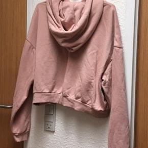 Rosafarvet DIVIDED hættetrøje str. L.  Kort model med gennemløb forlomme. Brystvidde 65 cm x 2, længde og Ærmer 55 cm