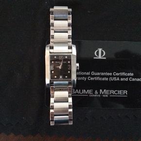 """Klassisk og smukt Baume et Mercier ur med safirglas og små fine diamanter i urkasse og på """"optrækkerpind"""". Købebevis og original æske samt ekstra led medfølger. Det skal have nyt batteri, derfor den lave pris, men virker som nyt. Nypris ca 20.000kr. Tjek størrelse på billeder"""