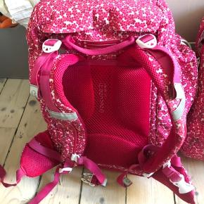 Skoletaske (foret ryg, indstillelige bæreremme) og gymnastik/turtaske til at klikke på stor taske eller bære for sig. Blomstret pink og hvid, meget fin stand. Penalhus kan tilkøbes for 50,-, bærer lidt flere brugsspor (blyantsmærker mv).