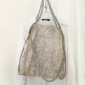 Taske i en lys beigenuanceret farve med sølvfarvet kæderem. Perfekt til sommer outfits ✨