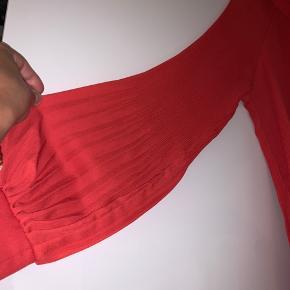 Rødorange top med plisse og fine ballonærmer