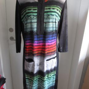 Smart kjole fra Jørli i friske farver. Den har lynlås ned foran og små lommer foran. Brystvidde 108cm Talje 98cm Det mønstrede stof består af: Lavet af 95% viskose og 5% stræk, det sorte stof er lavet af polyester og stræk. Se også mine andre annoncer, har mange forskellige størrelser.