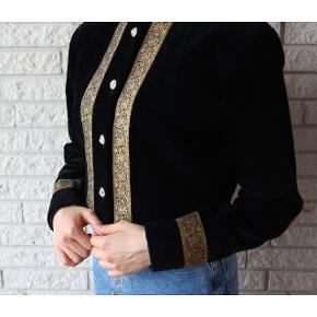 OH MY GOD! Eksklusiv sort velour skjorte/blazer fra 1980'erne med guldprint og bling bling knapper.  Skulderpuderne giver et V-look. Det er virkelig et guldfund. Den matcher både jeans, bukser og nederdele. Kan bruges i enhver anledning. Passer størrelse: 32-36. Pris: 380 kroner. 🌸