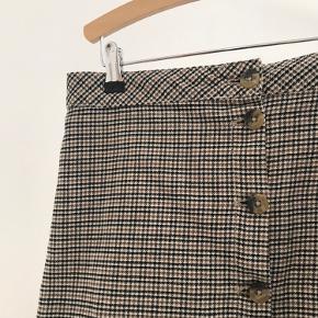 Nederdelen er i rigtig fin stand. Nederdelen har tern og knapper hele vejen ned i naturlignende stil.
