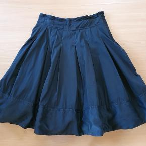 Flot sort knælang nederdel med masse af vidde og underskørt fra Karen Millen. Str. 10 UK eller 38. Materialet er bomuld og elastan, kant forneden er i silke. Livvidde 70 cm, længde 56 cm. Brugt 2 gange, som ny.