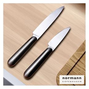 Eksklusivt Normann Copenhagen knivsæt Består af en urtekniv og en universalkniv  Æstetiske køkkenknive med bløde konturer og et fint netmønster, der opleves som en naturlig del af kniven og giver et godt greb om kniven. Vægtbalancen mellem blad og greb er fint afstemt, så kniven ligger godt og behageligt i hånden, selv når der lægges pres på kniven. Ideel til at skrælle og skære frugt, grønt, løg m.v. – den klarer alle daglige hakke- og snitteopgaver.  Knivene er håndsvejset i 100% rustfrit stål.  Universalkniv: H: 2,5 x L: 24,5 cm Urtekniv: H: 2,5 x L: 20 cm Praktisk til daglig slid og brug
