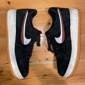 Nike air force 1 sko - str. 40, sort ruskind og med swoosh der er halvt hvidt og halvt kobber farvet. Brugt 2-3 gange, super god stand. Uden æske. Køber betaler for forsendelse - kan dog mødes efter aftale og handle på Amager for at bespare forsendelsen :)