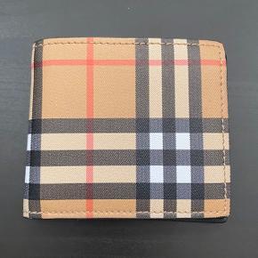 Burberry Vintage Check E-Canvas International Bifold Wallet. Sælges med dustbag og æske, uden kvittering, da det var en gave. Aldrig brugt, helt uden fejl/skader.  FAST PRIS: 1100 kr. + porto Lad være at byde under, tak. Bytter ikke. Kun seriøse henvendelser.