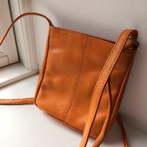 Orange lædertaske bestående af et stort rum + ét mindre samt et udvendigt rum uden lynlås. Remmen kan reguleres i længden. Købt i Italien. Ægte læder/genuine læder.   ▪️Sender gerne/køber betaler porto ▪️Returnerer ikke ▪️Kun fra dyrefrit hjem ▪️Køber betaler ts gebyr
