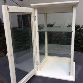 Fint gammelt glas skab / vitrine.  Købt i fransk antik butik da det var en del ad deres Interior.  Skabet har 4 sider med glass , en dør og 2 glass hylder. I pænt stand , men ny maling vil nok pynte.  Måler: 70 cm højt. 40 cm bred på alle træ sider.  Bredden af glasset er 36 cm.  Skal hentes V/ Nyhavn.   A White glass cupboard/ vitrine for porcelain/ jewelry or keep sakes. Was bought in French antique shop as a part of the interior.  White wood with glass on all 4 sides, on door opening, 2 glass shelves.  Measuring: 70 cm tall. 40 cm vide on The Wood. 36 cm on The glass sides.  Must be Pick up. Can not be delivered.