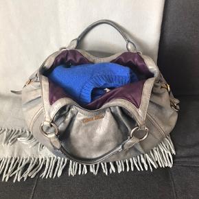 Ældre Miu Miu-model, som ikke fåes længere. Meget smuk patina, men har alligevel skrevet brugt. Det mørkelilla for skaber superflot kontrast til den grå-blå farve, som taskens læder har. Har forsøgt at tage billeder af alle detaljer - kvittering haves desværre ikke, men den er ægte.