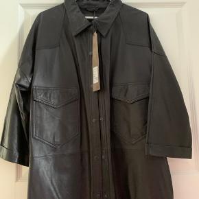 Super lækker sort skind kjole- skjorte - tunika som man vil.  I det blødeste skind. Helt ny med pris mærke på.  Kom med bud. Ny pris 2800kr.