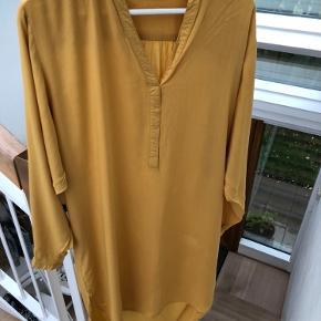 Smukkeste kjole fra Rabens Saloner i brændt gul. 100 % viskose. Den er længere bagpå. Super fin til bukser og skindbukser :)