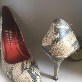 Mærke: Bronx Størrelse: 39 Farce: Krokodille Materiale: Læder Stiletten: Flot stilet sko med lang spids snude. Fest sko Stand: Skoen er aldrig brugt  Sælges kr 125