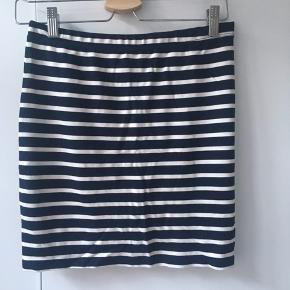 Mørkeblå nederdel med hvide striber.  Der er elastik i linningen.  Længde: ca. 43 cm