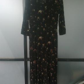 Varetype: maxi kjole med blomster maxikjole Farve: Brun blomstret blomster  Maxikjole med knapper hele vejen ned foran.  100 % viskose Sendes forsikret med dao mm andet aftales