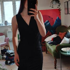 Smuk sort kjole fra Deviér (købt i samsø samsø) med wrapdetaljer og dyb nedskæring. Sidder tæt til kroppen og fremhæver former