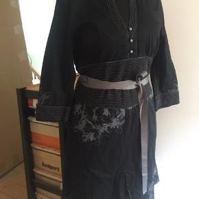Smuk kjole fra By Groth.  Oprindeligt en råhvid kjole, som er indfarvet i flot sort, så der findes næppe en kjole magen til. Koksgrå abstrakt blomsterprint langs kanter, på front, på ryg og på ærmer.   Flot blødt sort stof med en anelse stretch, som sikrer en skøn pasform. Koksgrå kontrastsyninger langs ærmekanter, udskæring og på det brede bærestykke i taljen. Lommer i siderne og aftageligt flot koksgrå strukturvævet satinbånd i taljen.   Råhvid lynlås i siden, så kjolen er nemmere at få over bryst og hofter. Rustikke runde metalknapper i udskæringen.  Str. XL, men da den er lille i størrelsen, er figursyet og sidder meget til, vil den ca. passe en str. 40/42 med en medium barm eller en str. 44 med en mindre barm.  God flot brugt stand, da den kun har været på en håndfuld gange til pæn brug ved bryllup/barnedåb.  En utrolig smuk kjole med de fineste detaljer. Skriv pb for ekstra nærbilleder. Nypris kr. 1499,95.  Pris ved afhentning Nordsjælland eller + porto.