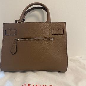 Sælger denne Guess håndtaske, der medfølger lang rem samt dustbag. Den er aldrig blevet taget i brug og er derfor helt som ny.