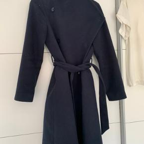 Super fin mørkeblå dobbeltradet frakke med revers som kan lukkes helt oppe med knaplukning så man ikke fryser.   Str 42