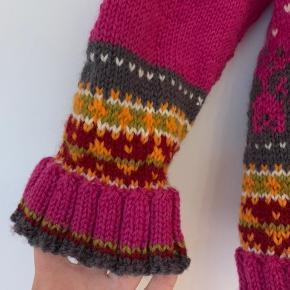 Ny hjemmestrikket sweater i ren uld str 122. Med det flyvende tæppe som logo foran.  Køber betaler Porto.