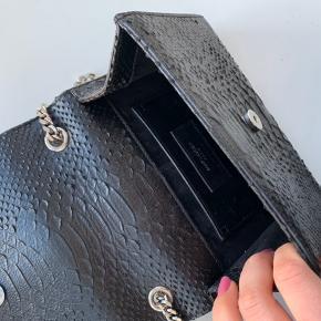 Smukkeste slangeskindstaske fra Yves Saint Laurent. Tasken har sølvhardware og er brugt minimalt.   Den perfekte selskabstaske.  Np. 10500,-  Mp. 5600,- Intet medfølger - står 100% inde for ægtheden    • Sender ikke flere billeder  • Prisen er eks. porto  • Kan hentes i Aarhus c  • Bruger normalt xs/34