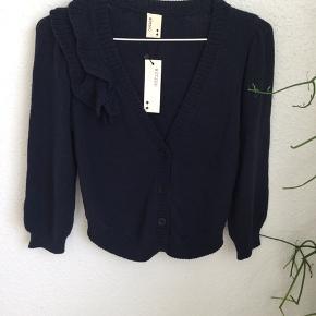 Fin strik cardigan med flæse detalje ved skulder. Farven er navy, blå, mørkeblå.  Vaskemærke mangler da det er en kollektionsprøve.
