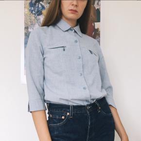 Lys blå vintage 70'er skjorte med bryslommer med lynlås. I god stand. Størrelse vides ikke, men er vist på str. 36.  Jeg bytter ikke, og tager kun imod bud i privatbesked 🌸