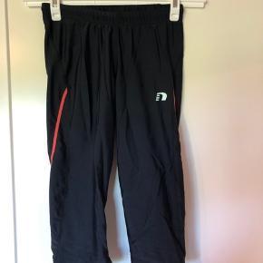 3/4 træningsbukser med meget elastik. De har en fin lyserød detalje ned ad benet og med en lille lomme bagpå. Der er snører i taljen.