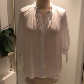 Fin skjortebluse med bindebånd på ærmerne. Let stribeeffekt i stoffet og flot fald.