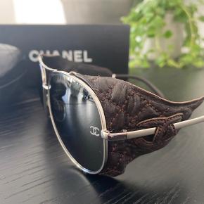 SJÆLDNE vintage Chanel Lambskin Aviator solbriller. Købt i 2014 på Vestiaire Collective med ægthedsbevis og perfekt stand-vurdering.  Jeg har brugt dem Max 10 gange, så der er ingen slemme eller synlige ridser.  Læderet er mørkebrunt og kan tages af.   Model: 4192q  Nypris omkring 1.040 US Dollars.  Set brugt til salg for omkring 600 US Dollars (i dag ville det være 4.230 kr.).   Prisen er fast - ellers beholder jeg dem hellere selv :)