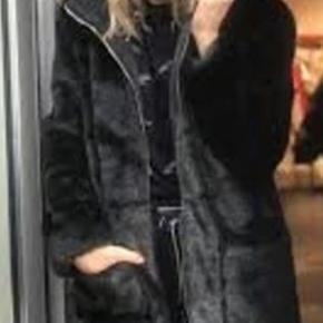 Skønneste sort fake pels fra Sofie Schnoor. Frakken fra Sofie Schnoor er syet i en lækker sort fake og har en dejlig hætte.  Helt ny og med mærke på endnu. Str. M