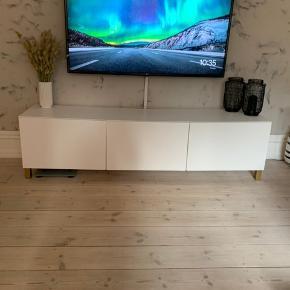 Sælger dette tv bord fra Ikea. Tv bordet er udsyret med guld ben. Det kan både hænge på væggen eller stå på gulvet. Som det kan ses på billederne er lågerne lidt skæve, da bordet buer lidt ned i midten og har lidt brugstegn. Men ellers står det flot.   Kom gerne med et bud da det skal sælges, da vi skal renovere.  Længde: 180 cm  Bredde: 41 cm inkl lågerne   Højde: 48 cm inkl ben