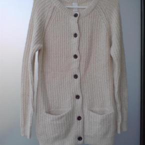 Varetype: cardigan strik trøje sweater Farve: Råhvid  Bryst 2 x 47 cm. uden at strække.  Længde 69 cm.    43% Polyacryl   27% Nylon  20% Bomuld  10% uld